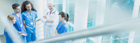 hospitales: futuros médicos jóvenes en un descanso durante el trabajo en el hospital. Hablar con el profesor más antiguo en el corredor
