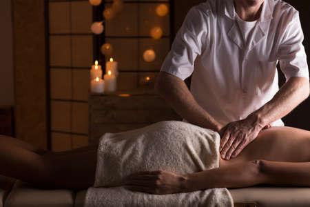 Mladá žena s masáž na její bederní páteře Reklamní fotografie