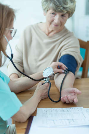 home care: Trusted doctor is taking her patients blood pressure
