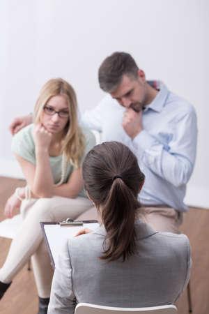terapia grupal: psicólogo de sexo femenino que ayuda pareja joven preocupante