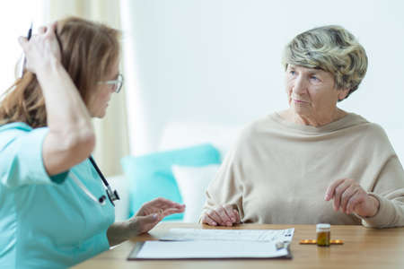 trusted: Elder lady is talking with her trusted doctor Stock Photo