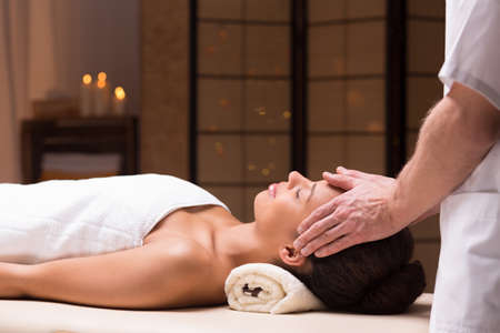 Beautiful relaxed girl at spa having face massage by male masseur Stock Photo