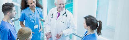 Anziani saggio professore a parlare con i suoi giovani studenti in stage medico