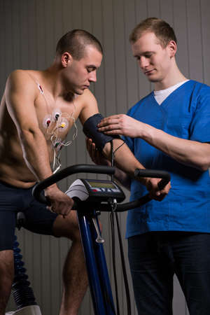 sportsperson: Sportsman on exercise bike and medic checking his blood pressure
