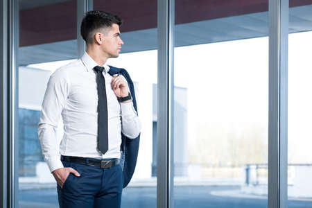 standing businessman: Handsome and elegant businessman standing in office building