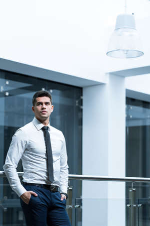 expectations: Elegant man leaning against railing in modern, office building Stock Photo