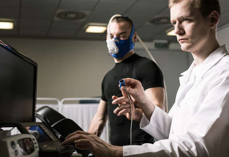 stress test: Sportsman in oxygen mask during annual check up and medic in white uniform Stock Photo