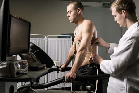stress test: Sportsman during medical test standing on treadmill and doctor in white uniform