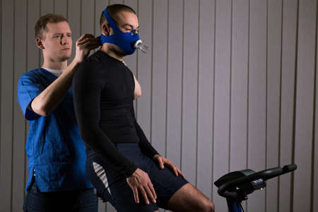 sportsperson: Sportsman training with oxygen mask, sitting on exercise bike and man in blue uniform