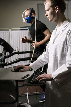 sportsman: Médico en uniforme blanco y deportista en masak oxígeno corriendo en la cinta Foto de archivo