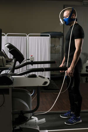 stress test: Young man during cardiac stress test standing with mask on treadmill