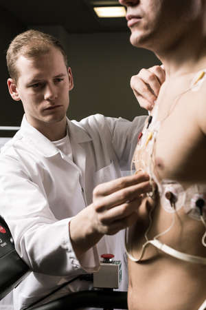 stress test: Close up of sportsman during medical test and doctor in white uniform Stock Photo