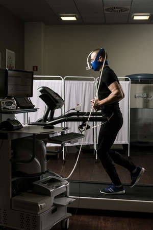 stress test: Sportsman in oxygene mask running on treadmill in medical office Stock Photo