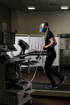 oxygene: Sportsman in oxygene mask running on treadmill in medical office Stock Photo