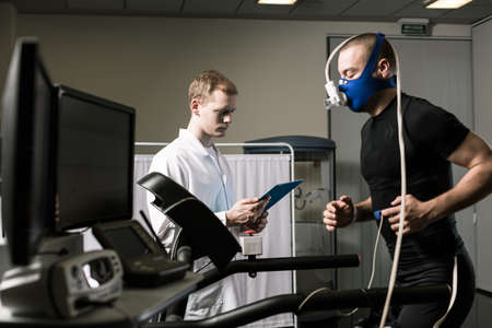 stress test: Athlete in oxygen mask running on treadmill and medic in white uniform