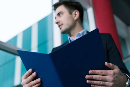 graduate: Young graduate holding his diploma, standing in modern building Stock Photo