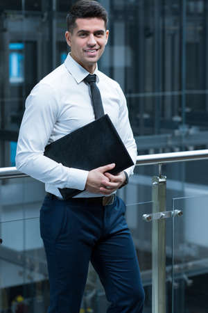 expectations: Elegant man leaning against railing in modern, office building, holding folder with documents Stock Photo