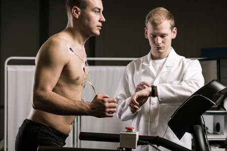Man läuft auf dem Laufband während der medizinischen Tests und Sanitäter in der weißen Uniform Lizenzfreie Bilder
