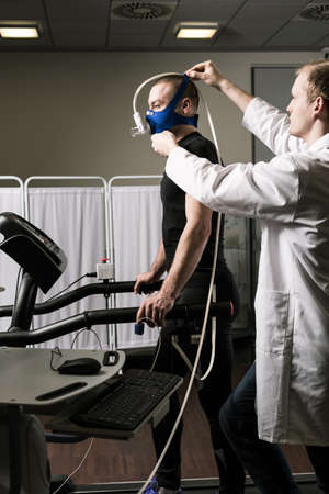 stress test: Sportsman in oxygen mask standing on treadmill during annual check up and medic in white uniform