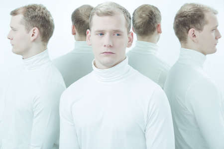 low self esteem: Sick, young man with split personality standing in white interior