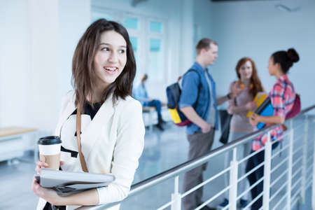 post secondary schools: Smiling student holding coffee and her notes, standing at college building