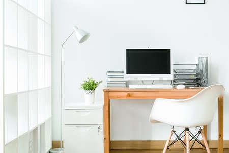 Studovna v bílé barvě s moderním, jednoduchým nábytkem
