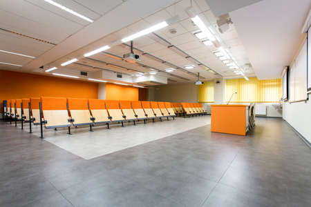 orange chairs: Spacious academic interior with wood chairs and desk with orange details