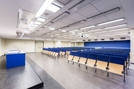 Light, spacious auditorium with blue details, wood chairs and desk 免版税图像