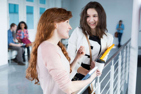 post secondary schools: Two students talking during break between academic classes Stock Photo