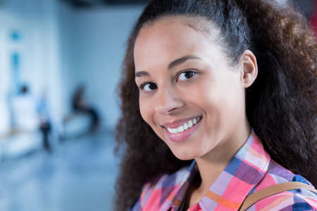 post secondary schools: Beautiful student smiling, standing at university building