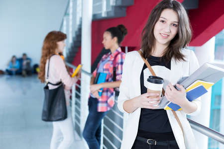 post secondary schools: Positive student holding cup of coffee and her notes