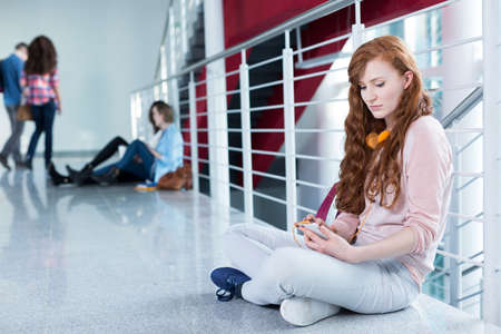 post secondary schools: Rouge student with cellphone and headphones sitting on floor at university building Stock Photo