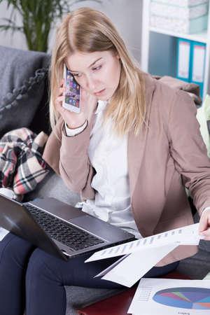 madre trabajando: madre ocupada trabajando en casa, hablando por teléfono celular, sentado en el sofá