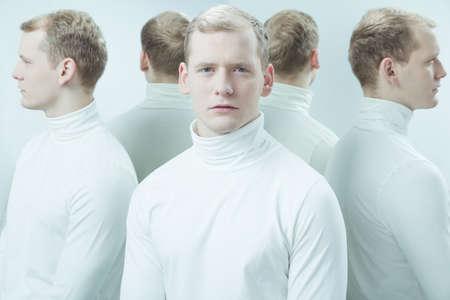 low self esteem: Duplicated image of mental hospital patient standing in light interior Stock Photo