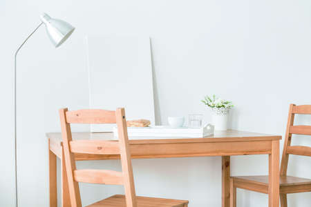 interior spaces: Light interior with simple wood chairs, table and modern standing lamp Stock Photo