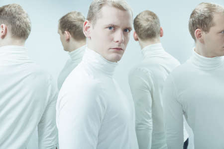 low self esteem: Duplicated image of man with mental problem, standing in white interior