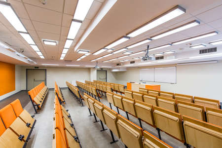 Spacious auditorium with orange, wood chairs and desk Stock Photo