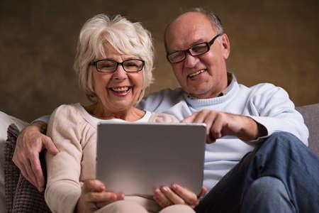 persona feliz: Foto de una pareja de ancianos felices usando una tableta