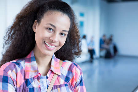 post secondary schools: Happy, afroamerican student standing at college building