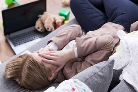 Müde Frau auf Sofa liegend, für das Gesicht mit ihren Händen, Laptop und Spielzeug auf dem Boden liegend