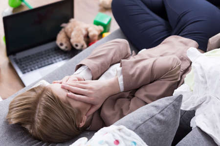 mess: Tired woman lying on sofa, covering face with her hands, laptop and toys lying on the floor