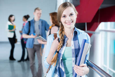 post secondary schools: Beautiful, young girl at university holding her notes, smiling Stock Photo