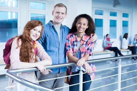 estudiantes universitarios: Tres estudiantes de pie junto al edificio de la universidad