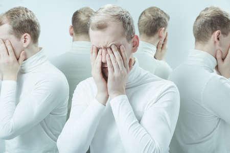 ansiedad: El hombre con problemas mentales que cubre su cara con las manos, imagen duplicada
