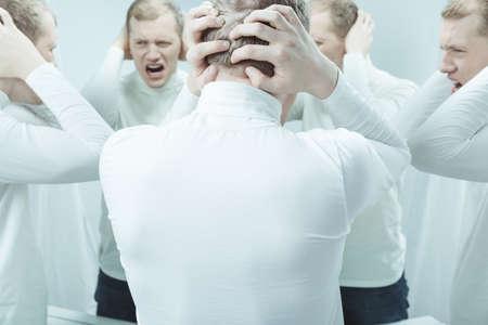 esquizofrenia: Imagen de asilo voces de audición del paciente duplicado en la cabeza, que cubre los oídos con las manos Foto de archivo