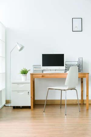 wood flooring: Study room with wood flooring and simple, light furniture