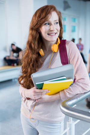 post secondary schools: Rouge woman with notes and headphones standing in modern college building