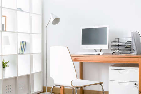 Light home office with simple wood desk, chair, computer and standing lamp Stock Photo
