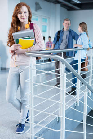 secondary education: Rouge, academic girl holding her notes, standing against railing in college building