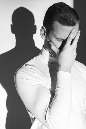 in thought: Sad man covering face with his hand and his shadow on the wall, photo in black and white
